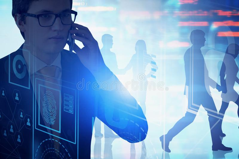 Man in glasses on phone, online security concept. Serious young man in suit and glasses talking on smartphone. Business people silhouettes in background. Double stock photography