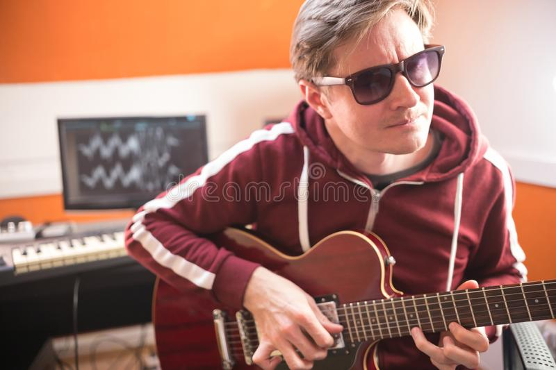 A man in glasses playing guitar and recording a song in the studio. Mid shot stock photo