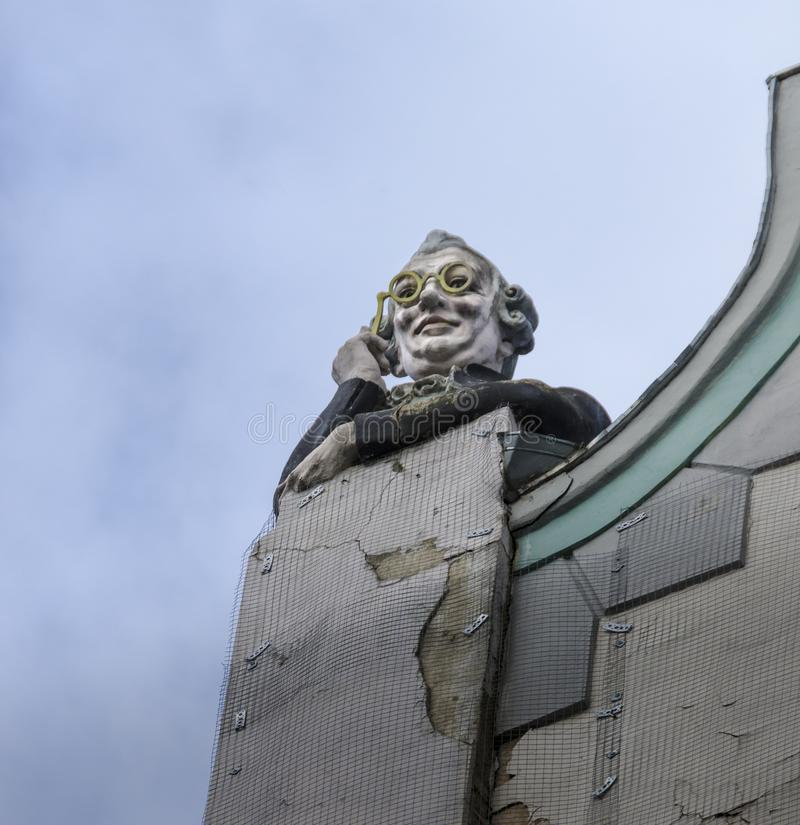 Man with glasses sculpture, Tallinn, Estonia. Sculpture of a man looking through opera glasses, on top of a building in the old town of Tallinn, Estonia royalty free stock image