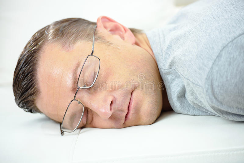 Man with glasses sleeping on desk royalty free stock photo
