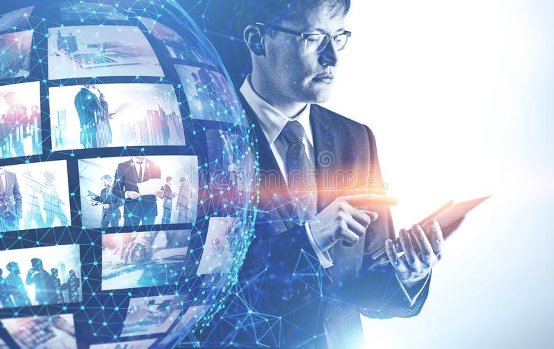 Man in glasses using streaming interface. Serious young men in glasses and suit using tablet with double exposure of futuristic video streaming interface. Hi stock image