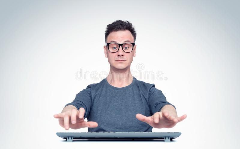 Man in glasses working at the computer, his hands hover over the keyboard while typing. Front view. Man in glasses working at the computer, his hands hover over stock photo
