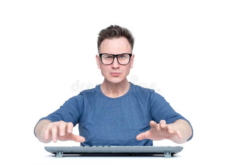 Man in glasses working at the computer, his hands hover over the keyboard while typing, isolated on white background. Front view. Man in glasses working at the royalty free stock photo