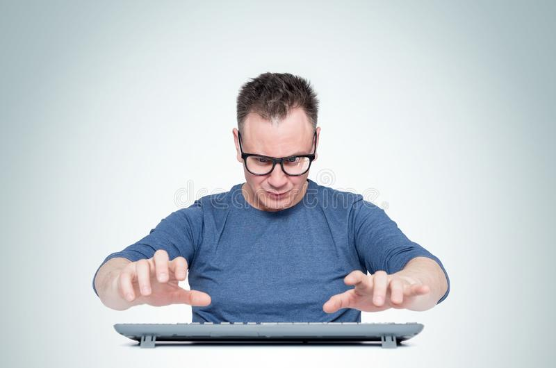 Man in glasses working at the computer, his hands hover over the keyboard while typing, on light background. Front view. Man in glasses working at the computer stock image