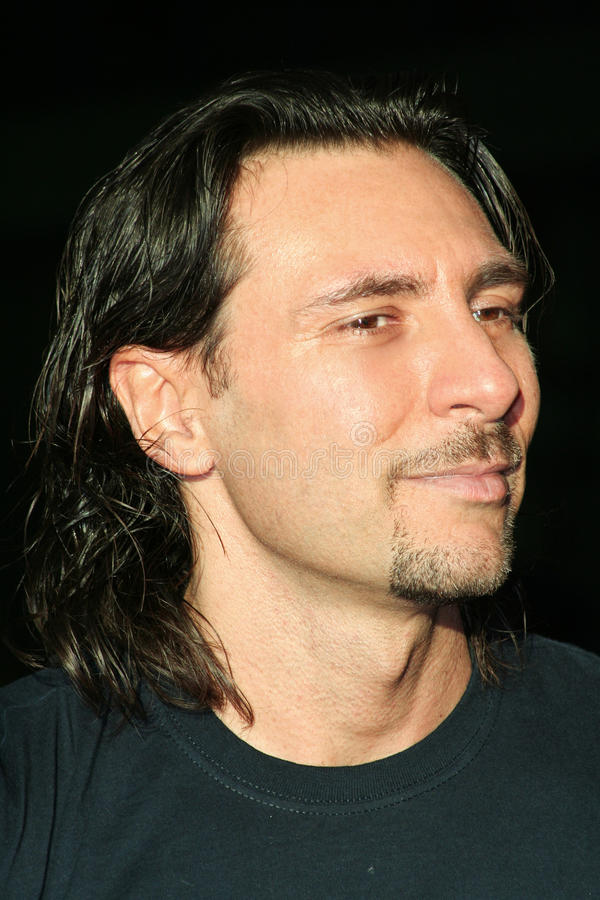 Man with goatee and long hair on black background stock photography
