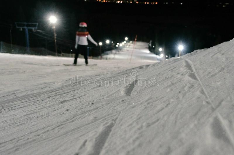 Man goes down the mountain on a snowboard slope next to the lift. Evening snowboarding. Man goes down the mountain on a snowboard slope next to the lift stock photos