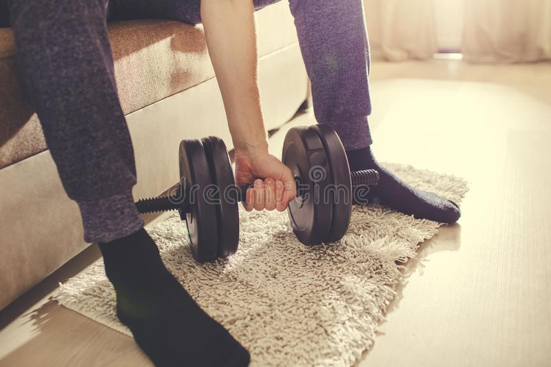 A man goes in for sports at home with dumbbells.  royalty free stock image