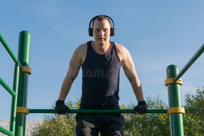 A man goes in for sports on the horizontal bar listening to music on headphones on the street in fine weather royalty free stock images