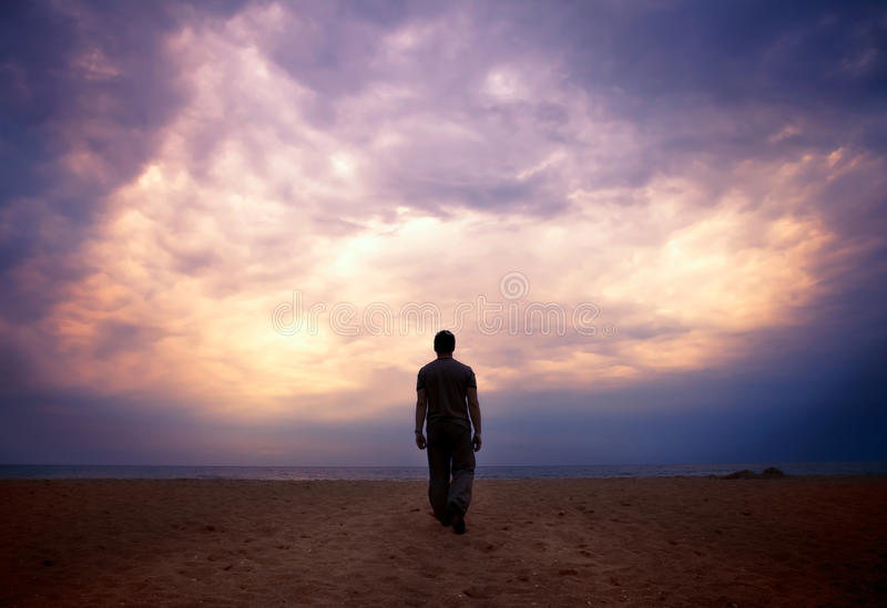 Man goes to the sea under cloudy sky stock images