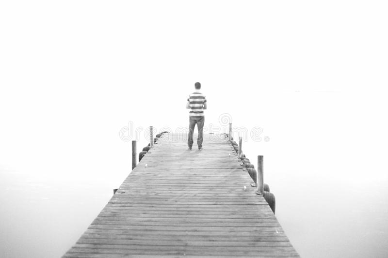 A man goes on the wooden pier in high key. Black and white royalty free stock image