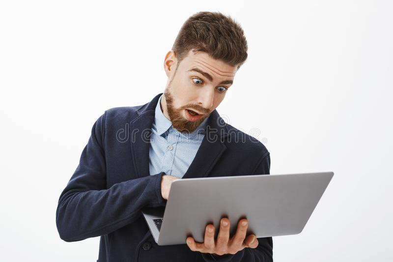 Man going crazy, being in rush working on project. Anxious troubled good-looking male with beard in suit holding laptop stock images