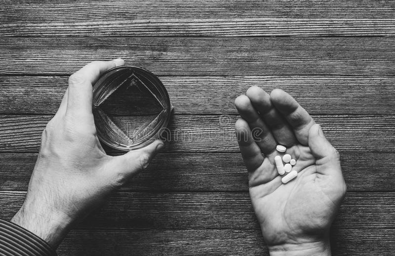 The man is going to eat pills and capsules and taken with water, black white photos. Top view stock images