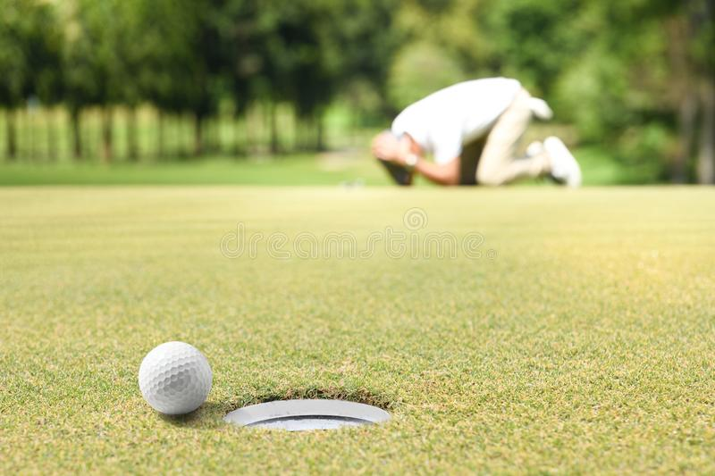 Man golfer feeling disappointed after a putted golf ball missed the hole royalty free stock photography