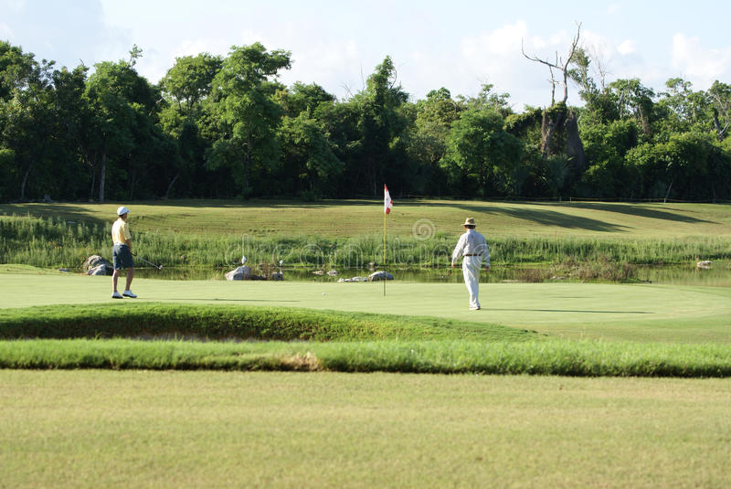 Man Golfing with Caddy. Man on beautiful golf course in Cozumel Mexico golfing with his caddy royalty free stock photo