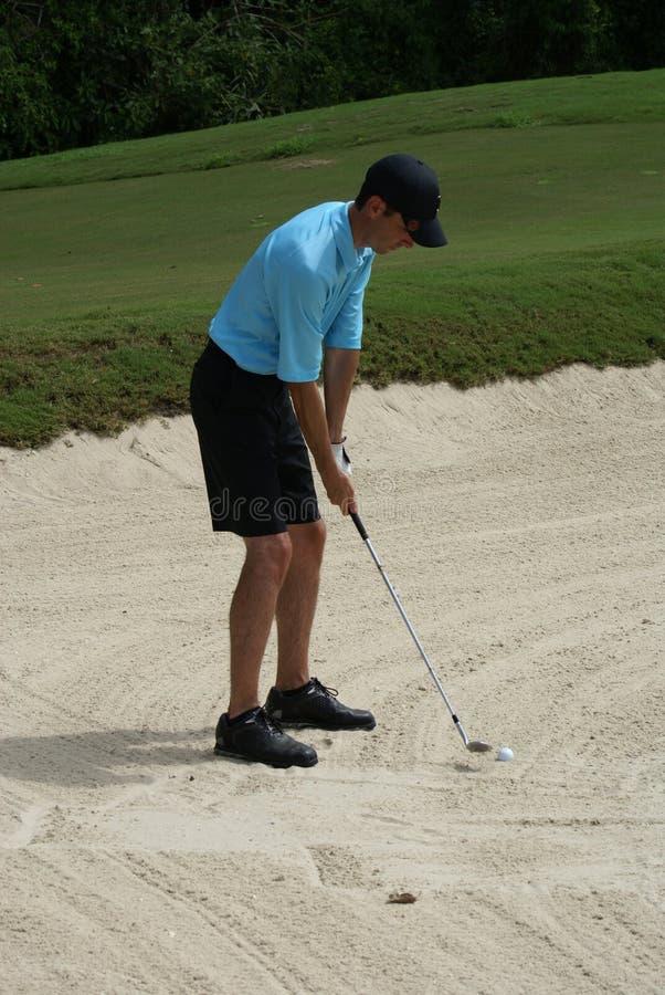 Man Golfing From Sand Bunker stock photos