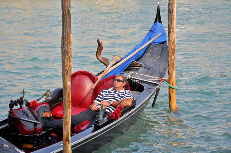 Man on Gondola Having a Rest. VENICE, ITALY - SEPTEMBER 30: Gondolier has a rest in gondola on September 30, 2009 in Venice, Italy. Profession of gondolier is stock photos