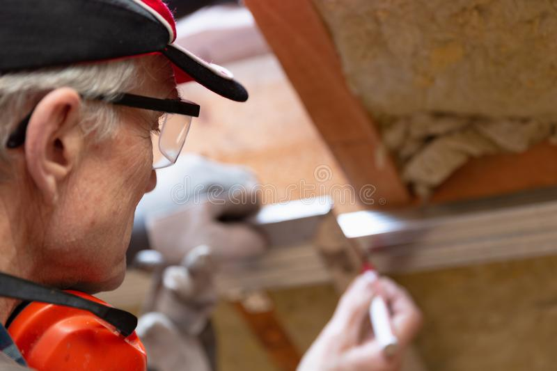 Man in googles making a mark on metal frame on unfinished attic ceiling. Attic insulation and renovation royalty free stock image