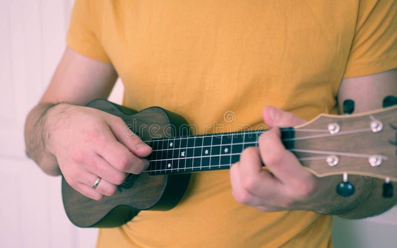 Man grabben som spelar ukulelet arkivfoto
