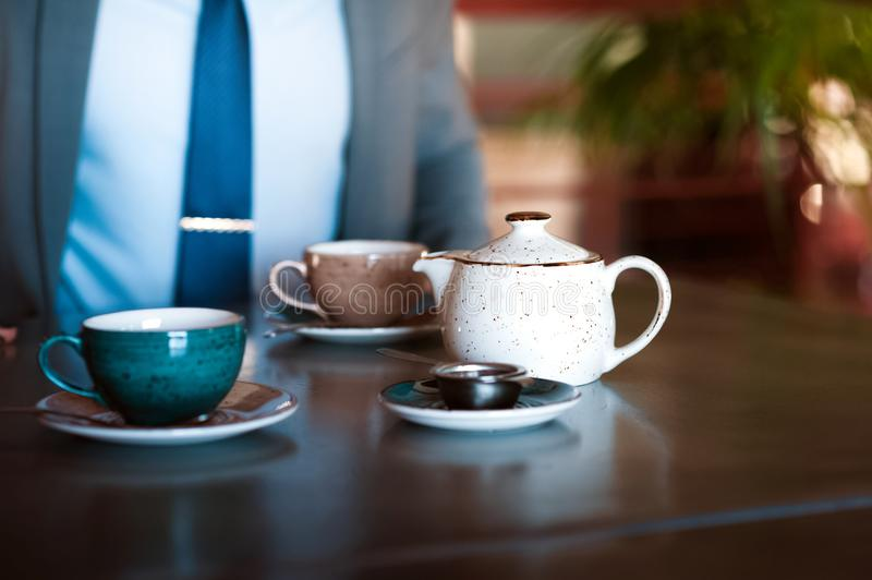 A man in a gray business suit and tie is sitting at the table and pouring tea from the brewer. royalty free stock image