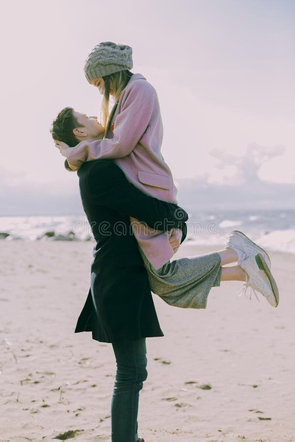 Man in Gray Coat Carrying Woman Wearing Pink Coat in Beach Near Shoreline and Body of Water stock photos