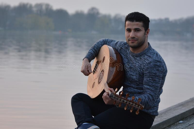Man In Gray Crew Neck Sweatshirt And Black Pants Sitting In Gray Concrete Holding String Instrument Near Body Of Water Free Public Domain Cc0 Image