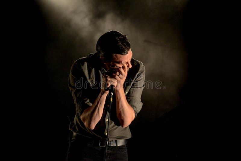 Man in Gray Dress Shirt Holding Mic in Dark Room stock photo