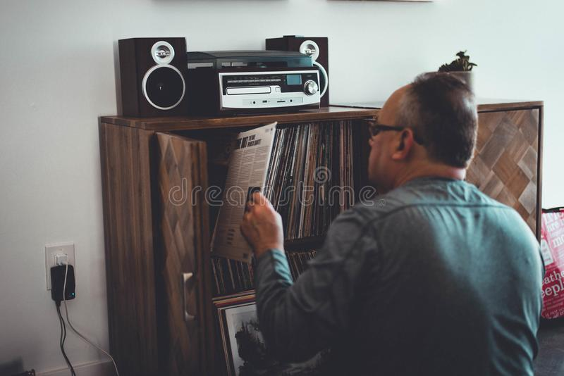 Man in Gray Longsleeve Shirt Holding Book in Front of Brown Wooden Book Case stock photo