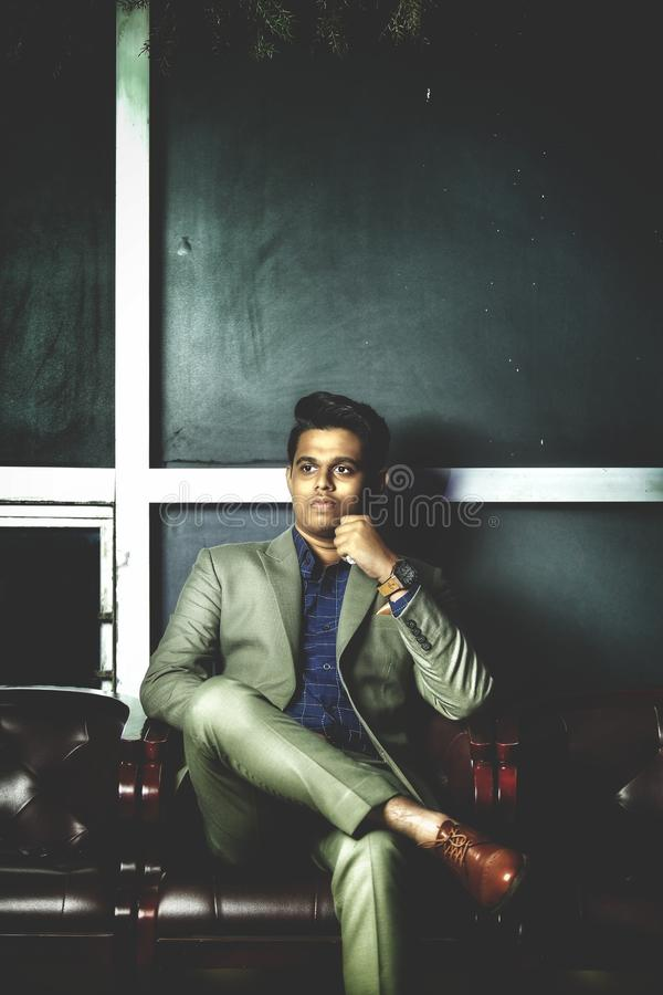 Man in Gray Notch-lapel Suit Jacket With Dress Pants While Sitting on Armchair stock image