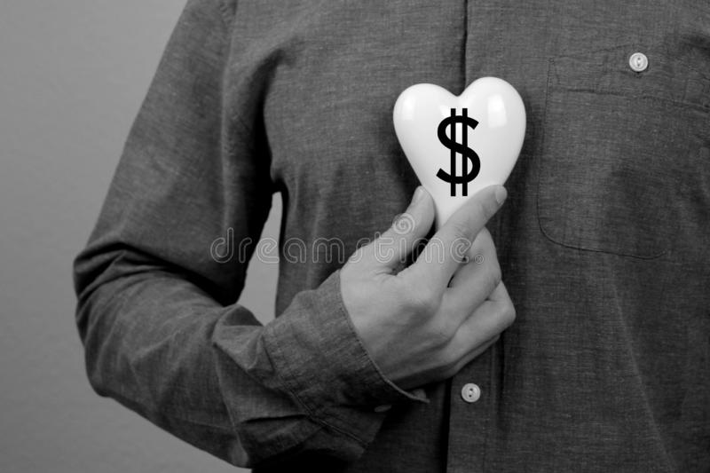 Man in a gray shirt in his hand near his chest holds a white heart with a dollar symbol, the concept of commercialism, self- royalty free stock photos