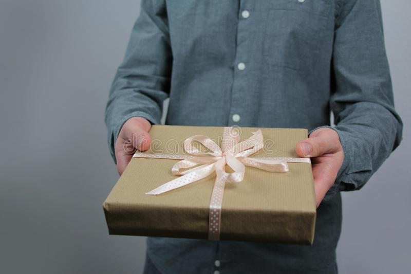 Man in a gray shirt in one hand holds a box with a gift, concept of celebrating Valentine`s day, mother, father, thanksgiving royalty free stock image