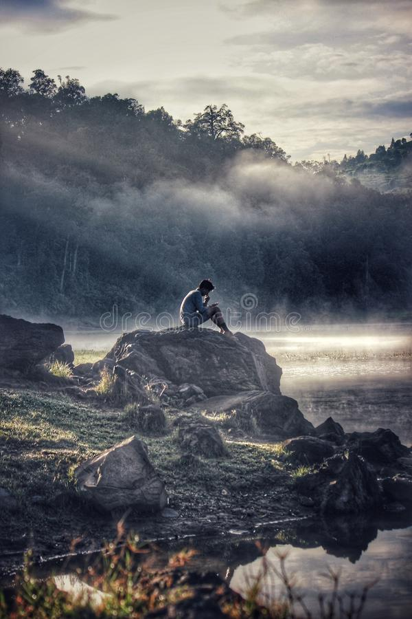 Man in Gray Shit Sitting on Rock Boulder stock photo