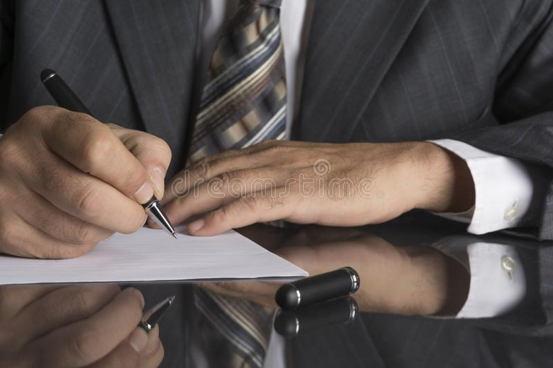 Man in gray suit holds a metal pen stock images