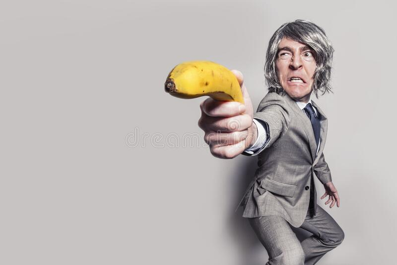 Man in Gray Suit Jacket Holding Yellow Banana Fruit While Making Face royalty free stock photography