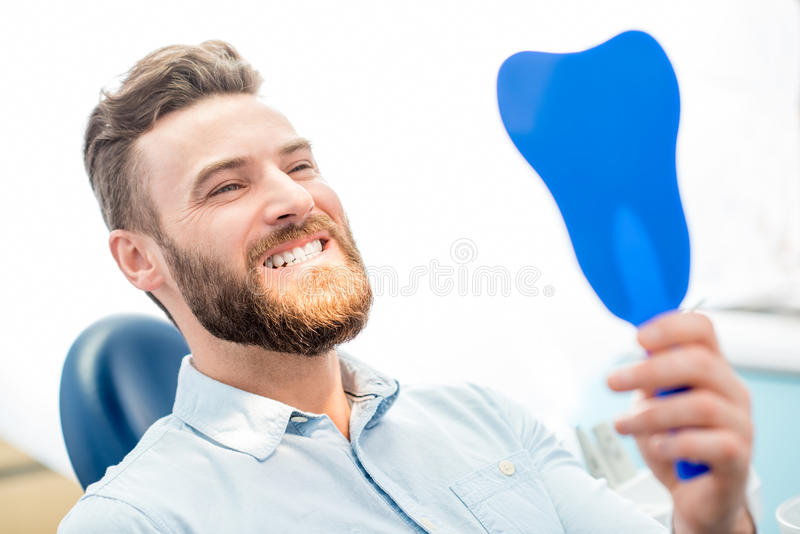 Man with great smile at the dental office. Handsome male patient looking at his beautiful smile sitting at the dental office royalty free stock photography
