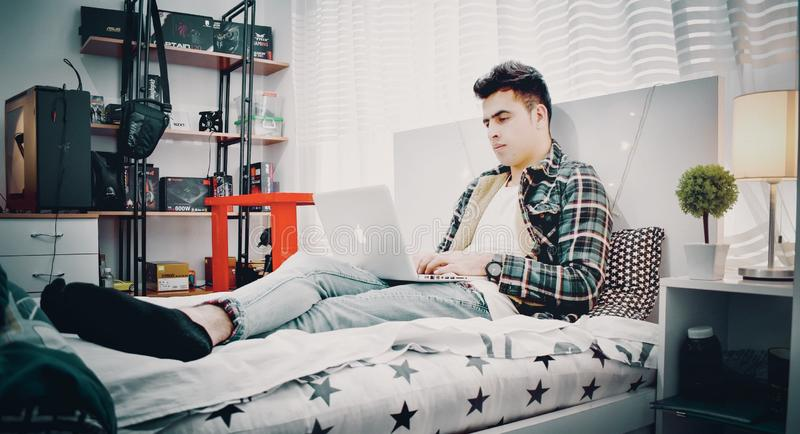 Man in Green, Blue, and Black Plaid Sports Shirt Sitting on Bed Using Silver Macbook royalty free stock photography