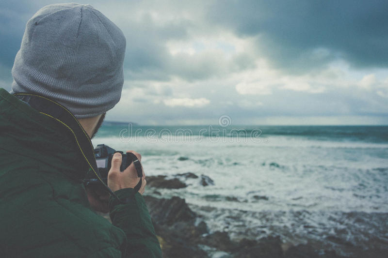 Man In Green Hoodie Holding Dslr Camera Near Seashore Under Gray Clouds Free Public Domain Cc0 Image