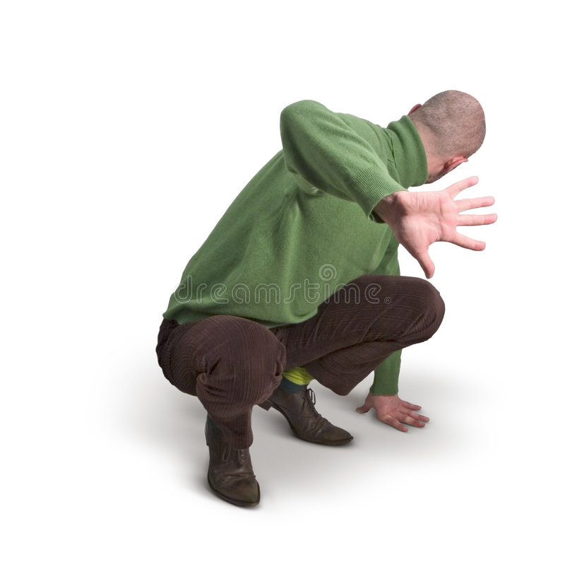 Man in Green Jumper 22. Man in green jumper crouching, turning head, hand outstretched stock image
