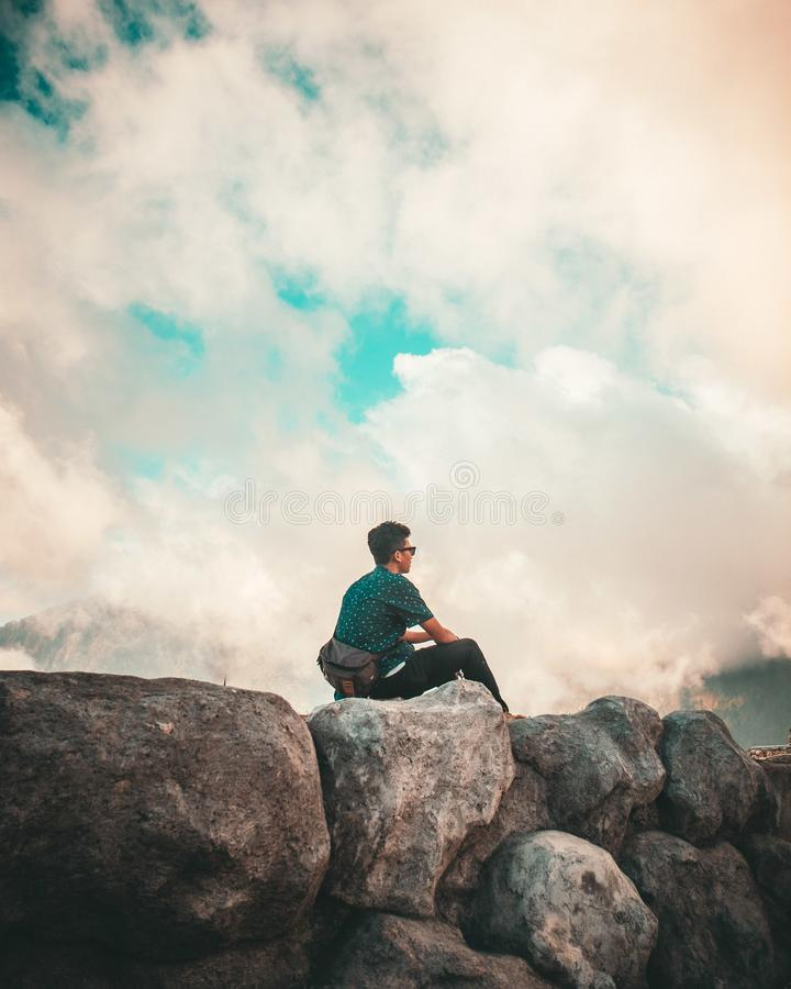 Man in Green Shirt and Black Pants Sitting on Top of Rock Cliff Under White Clouds stock photos