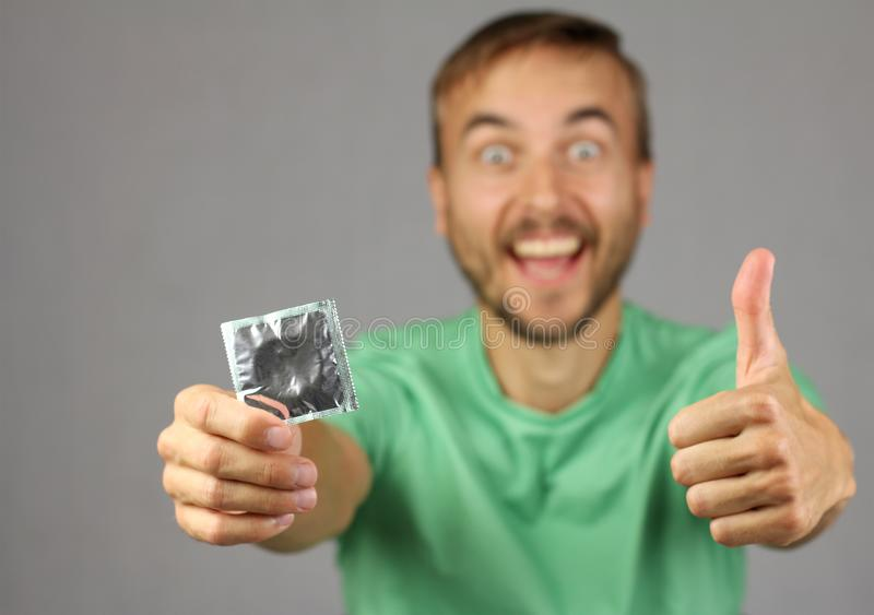 man in green shirt holds a new condom in hand, make gesture thumb up, joy and anticipation of pleasure stock photo