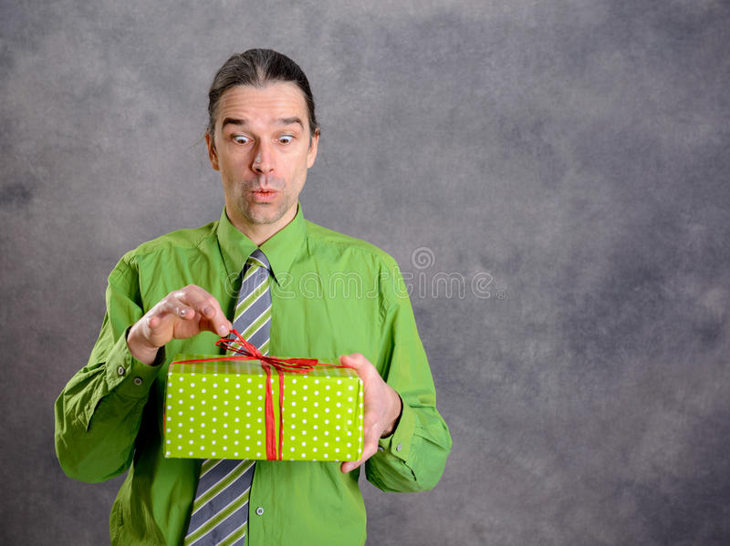 Man in green shirt and necktie with green gift box is surprised stock image