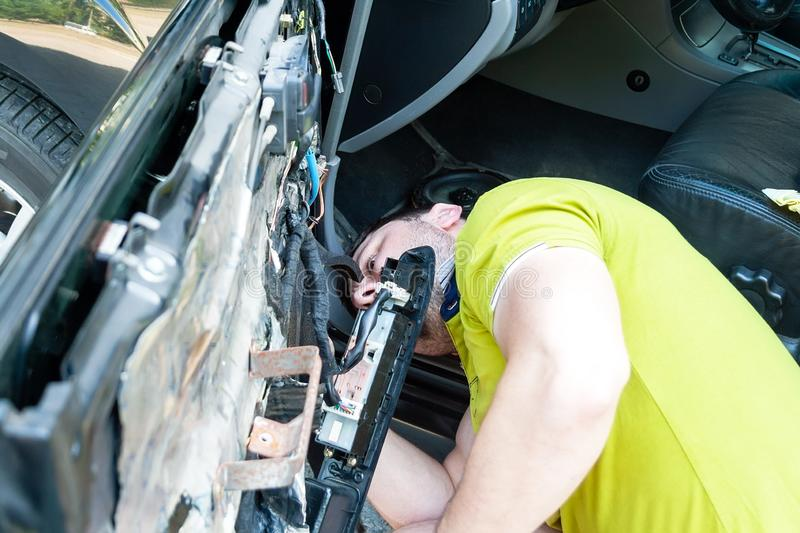 A man in a green t-shirt is looking from below at the car door to be disassembled in order to repair the power window royalty free stock images