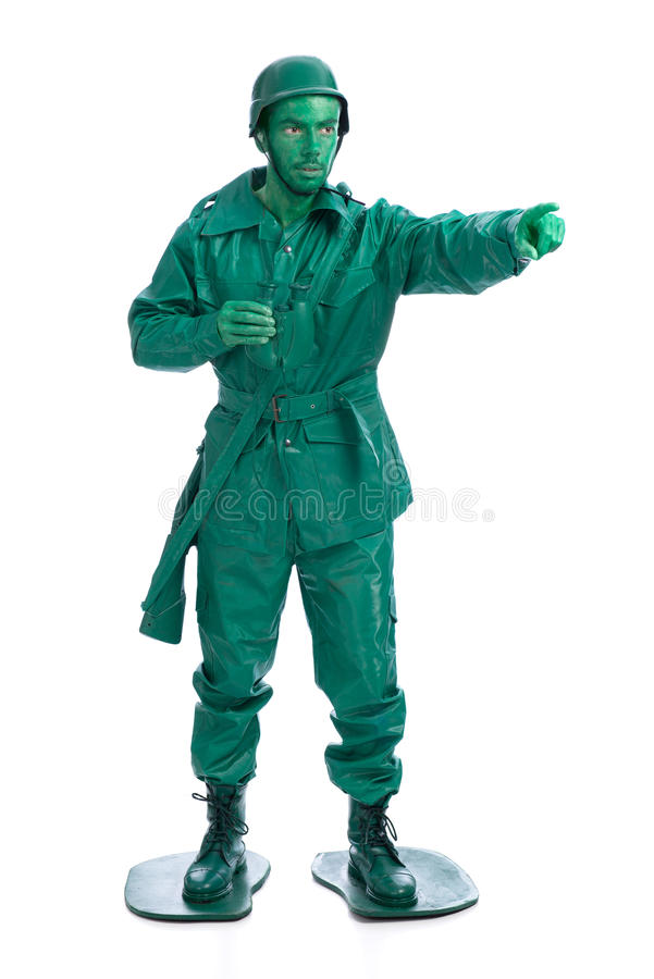 Man on a green toy soldier costume. With riffle poiting with his forefinger isolated on white background stock image