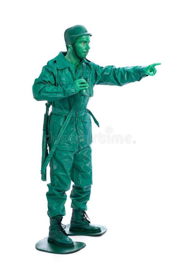 Man on a green toy soldier costume. With riffle poiting with his forefinger isolated on white background royalty free stock photography