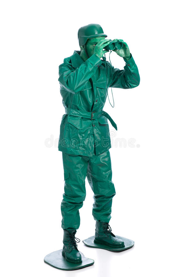 Man on a green toy soldier costume. Standing with binocolous isolated on white background royalty free stock images