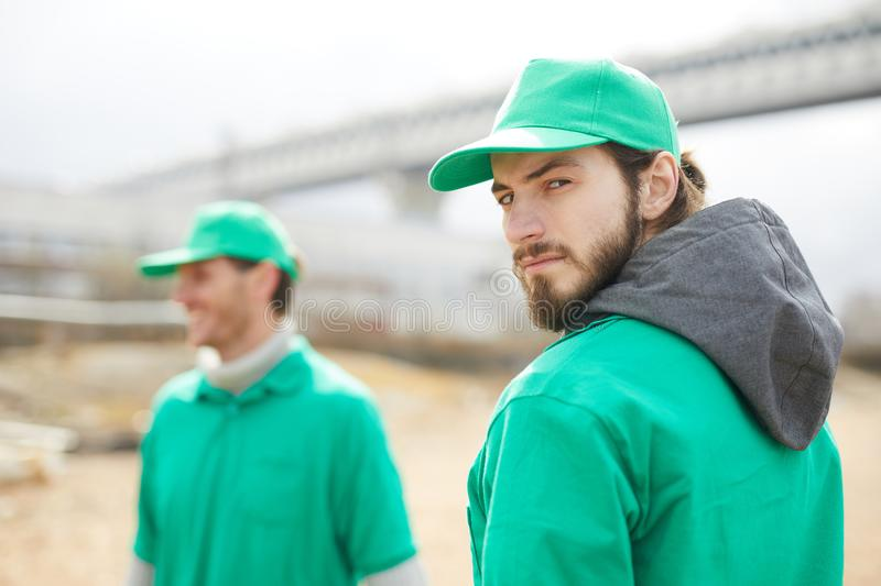 Man in green uniform looking at camera. Side view of volunteer in green uniform standing and looking at camera stock image