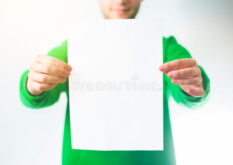 Man in greenery sweatshirt smile, Hand holding Blank A4 Flyer, D stock photo