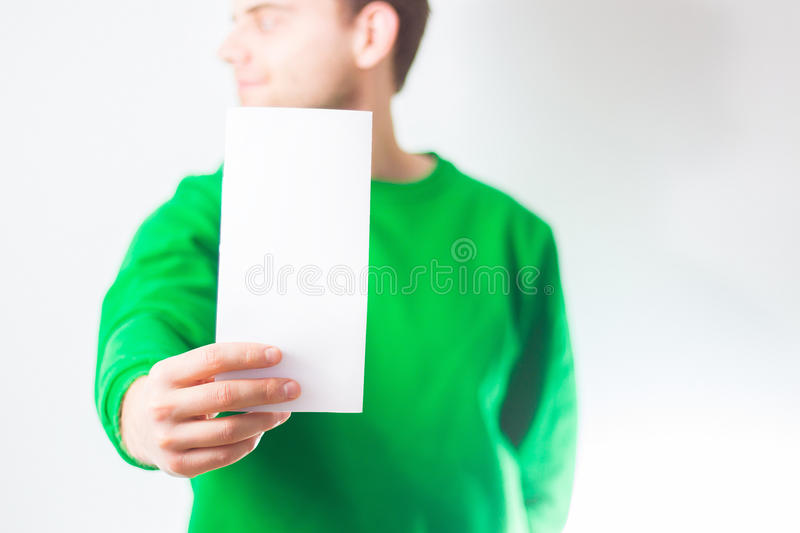 Man in greenery sweatshirt smile, Hand holding Blank A4 Flyer, D. L, A5, square, Invitation, brochure booklet, pamphlet, fold offset paper, design, mock up royalty free stock photos