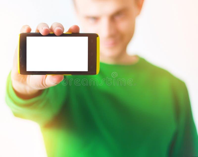 Man in greenery sweatshirt smile, Hand holding smart phone with stock photo