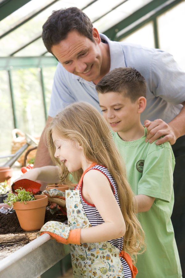 Download Man In Greenhouse Helping Two Young Children Royalty Free Stock Photography - Image: 5935417