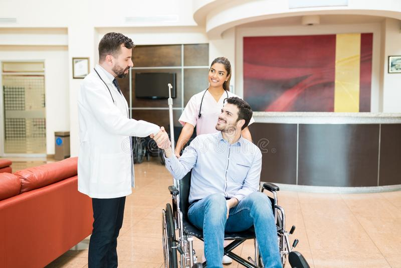 Man Greeting Goodbye To Doctors At Hospital Lobby royalty free stock image